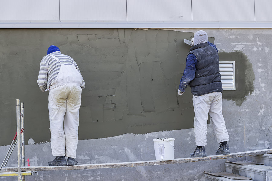 Stucco repairing in a business area by two professional